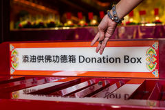 Hand dropping coins in donation box Stock Images