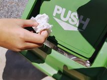 Hand Dropping Tissue Paper into Green Plastic Trash Bin with Push Word on Lid. Close-up Hand Dropping Tissue Paper into Green Plastic Trash Bin with Push Word on stock images
