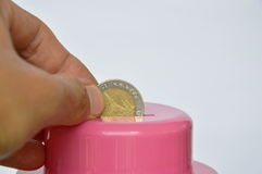 Hand drops Thai coin in pink piggy bank Royalty Free Stock Images