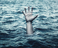 Hand of drowning man in sea Stock Image