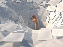 Hand drowning in paper sheets Stock Image