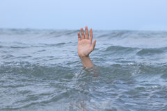 Hand drowning in the sea Stock Photos