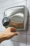 Hand dryer. In the picture we see a hand dryer and a hand royalty free stock images