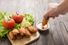 Hand dunk chicken hot wings in dipping sauce on wooden. Royalty Free Stock Image
