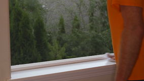 Hand dusting a window sill and window tracks with a cloth to reduce allergens for a healthier home. stock footage