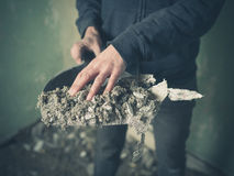 Hand with dustpan full of rubble Royalty Free Stock Images