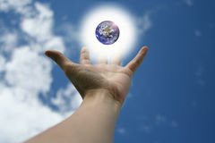 Hand and Earth. Outreached hand with a glowing earth floating above Royalty Free Stock Photography