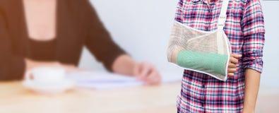 Hand in einem Riemen mit dem gebrochenen Arm in der Grünform lokalisiert auf blurre stockfotografie