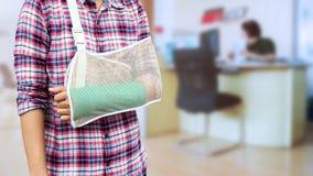 Hand in einem Riemen mit dem gebrochenen Arm in der Grünform lokalisiert auf blurre lizenzfreie stockbilder