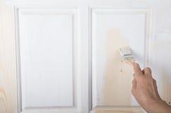 Hand einer älteren Frau mit einem Pinsel mit weißem Farbe doo Stockfoto