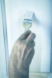 Hand einer älteren Frau mit einem Pinsel mit weißem Farbe doo Lizenzfreie Stockbilder