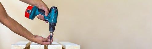 Hand einer Arbeitskraft schraubt eine Schraube in einem hölzernen Brett mit cordles Lizenzfreie Stockfotografie