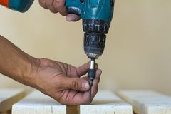 Hand einer Arbeitskraft schraubt eine Schraube in einem hölzernen Brett mit cordles Lizenzfreies Stockfoto
