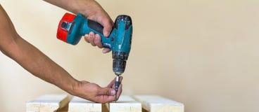 Hand einer Arbeitskraft schraubt eine Schraube in einem hölzernen Brett mit cordles Stockfotos