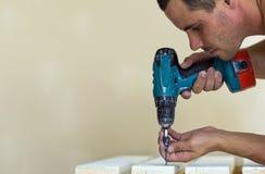 Hand einer Arbeitskraft schraubt eine Schraube in einem hölzernen Brett mit cordles Lizenzfreie Stockfotos