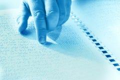 Hand einer blinden Person, die etwas Blindenschrift-Text berührt die Entlastung liest Duotone Lizenzfreies Stockbild