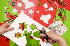 Hand einer Frau, die eine weiße Pappe mit Weihnachten schneidet, formt , Sterne und Glocken Lizenzfreie Stockfotografie