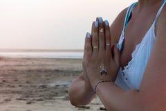 Hand einer Frau, die in einer Yogahaltung auf dem Strand bei Sonnenuntergang meditiert Lizenzfreie Stockbilder