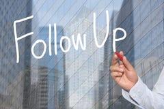Hand einer Geschäftsmannhand gezeichnet einem Wort des Konzeptes der weiterer Verfolgung Stockbild