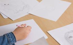 Hand einer Kinderzeichnung auf Weißbuch Stockbild