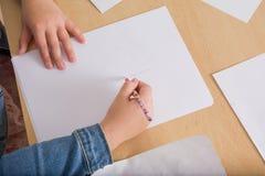 Hand einer Kinderzeichnung auf Weißbuch Lizenzfreies Stockbild