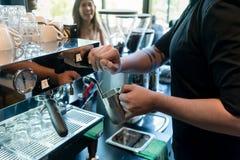Hand eines barista, das einen rostfreien Becher hält lizenzfreies stockfoto