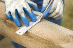 Hand eines Bauarbeiters zeigt mit einem Bleistift den Abstand auf einem hölzernen Rand Lizenzfreie Stockbilder