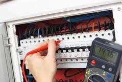 Hand eines Elektrikers mit Vielfachmessgerätsonde an einem elektrischen Schalter Stockfotografie