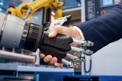 Hand eines Geschäftsmannes, der Hände mit einem Android-Roboter rüttelt lizenzfreie stockfotografie
