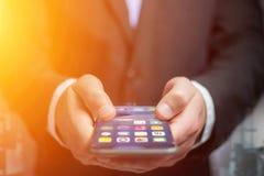 Hand eines Geschäftsmannes, der schwarzen Smartphone mit dem Betrieb von s hält Stockfotografie