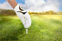 Hand eines Golfspielerplatzgolfballs auf dem T-Stück auf Fahrrinne stockfoto