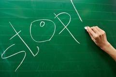 Hand eines jungen Mädchens, welches das Wort HALT auf die grüne Schulbehörde schreibt Stockbilder