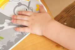 Hand eines Kindes auf einer Tabelle mit einem Bild Stockfoto