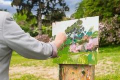 Hand eines männlichen Malers, der draußen im Park oder im Garten arbeitet Stockbild