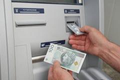 Hand eines Mannes, der Bankwesenmaschine verwendet Stockbild