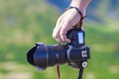 Hand eines Mannes, der Berufsdigitalkamera auf unscharfem gre hält Lizenzfreie Stockbilder