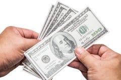 Hand eines Mannes, der eine aufgelockerte Handvoll von 100 Dollar hält Lizenzfreie Stockfotos