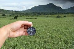 Hand eines Mannes, der einen Kompass in den grünen Wiesen an der Landschaft hält stockfotos