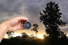 Hand eines Mannes, der einen Kompass im Abendsonnenuntergang an der Landschaft hält Stockfoto