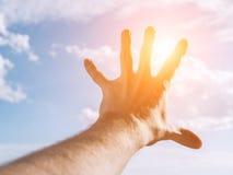 Hand eines Mannes, der in Richtung zu zum Himmel erreicht Stockfotografie