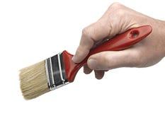 Hand eines Mannes, die einen Malerpinsel anhält Lizenzfreies Stockbild