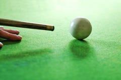 Hand eines Mannsnookerspielers streben weißen Ball an Stockbild