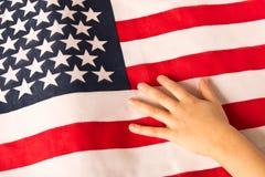 Hand eines wenigen Mädchens auf dem Hintergrund der amerikanischen Flagge Das Konzept von Patriotismus lizenzfreie stockbilder