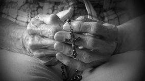 Hand of elder woman holding rosary while praying. Senior woman holding a rosary in her old hands while praying, Christian daily devotional of Catholic female Stock Images