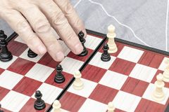 Hand of an elderly senior woman playing chess close up, entertainment and intellectual activity for retired people concept stock photography