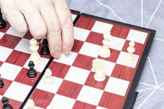 Hand of an elderly senior woman playing chess close up, entertainment and intellectual activity for retired people concept royalty free stock photo