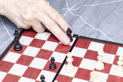Hand of an elderly senior woman playing chess close up, entertainment and intellectual activity for retired people concept royalty free stock photos