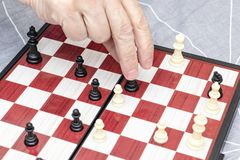 Hand of an elderly senior woman playing chess close up, entertainment and intellectual activity for retired people concept royalty free stock image