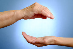 Hand of elderly woman above young woman's hand. On blue background Stock Photography
