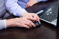 Hand of an elderly woman and a boy's hand holding a computer mouse Royalty Free Stock Photos